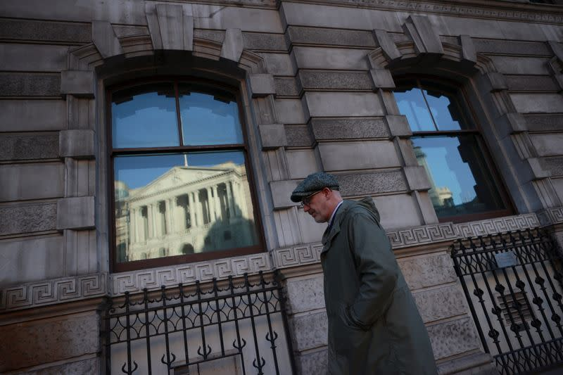 FILE PHOTO: A man walks past a window reflecting the Bank of England, in London
