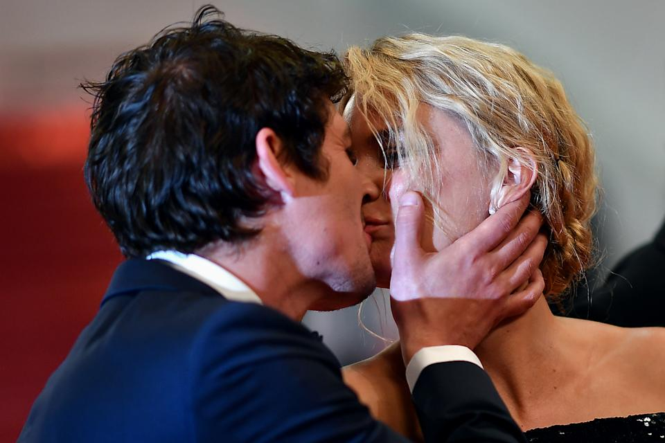 French-Canadian actor Niels Schneider (L) kisses his partner Belgian actress Virginie Efira as they leave the Festival Palace after the screening of the film
