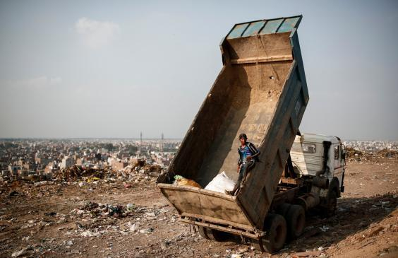 A waste collector stands inside a truck (Reuters)