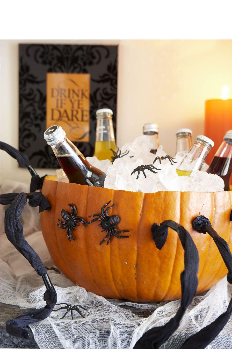 <p>Cut a large pumpkin in half and scoop the insides out of the bottom portion. Fill with ice and decorate it with faux spiders, and you've got the spookiest drink display on the block.</p>