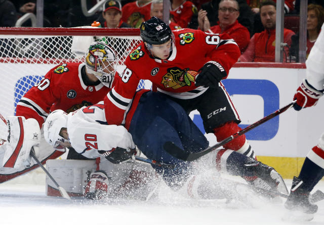 Washington Capitals center Lars Eller (20) is pushed down to the ice by Chicago Blackhawks defenseman Slater Koekkoek (68) during the first period of an NHL hockey game Sunday, Jan. 20, 2019, in Chicago. (AP Photo Nuccio DiNuzzo)