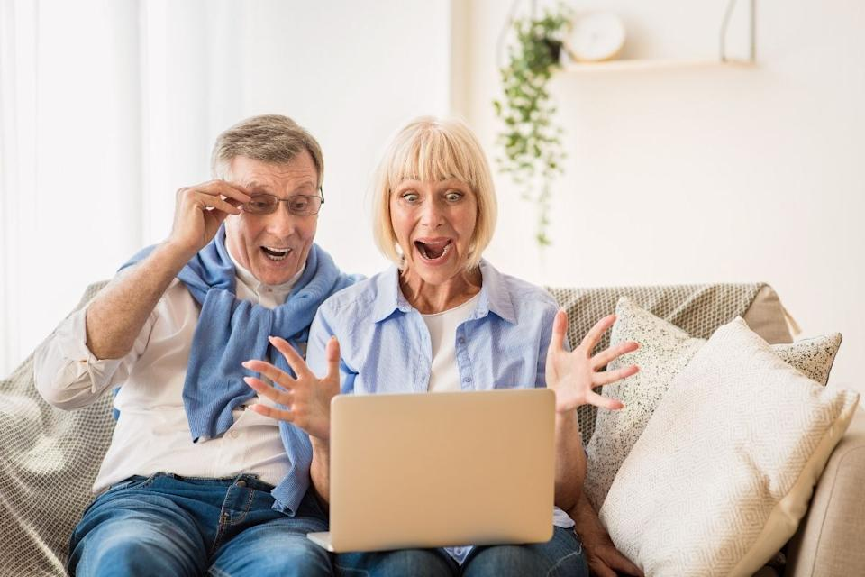 Middle aged couple celebrate lottery win looking at laptop. Source: Getty Images