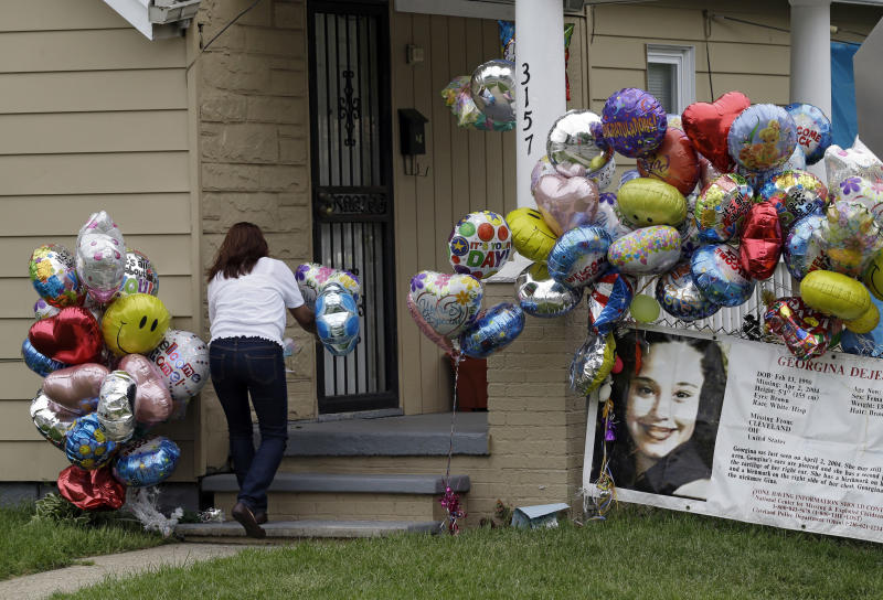 Culema Nevarez adds balloons to a growing tribute outside the home of Gina DeJesus in Cleveland, Friday, May 10, 2013. DeJesus was freed Monday from the home of Ariel Castro where she and two other women had been held captive for nearly a decade.  (AP Photo/Mark Duncan)