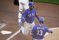 Texas Rangers' Isiah Kiner-Falefa, left, is greeted by Joey Gallo as he scores on a hit by Adolis Garcia in the first inning of a baseball game against the Minnesota Twins, Tuesday, May 4, 2021, in Minneapolis. (AP Photo/Jim Mone)