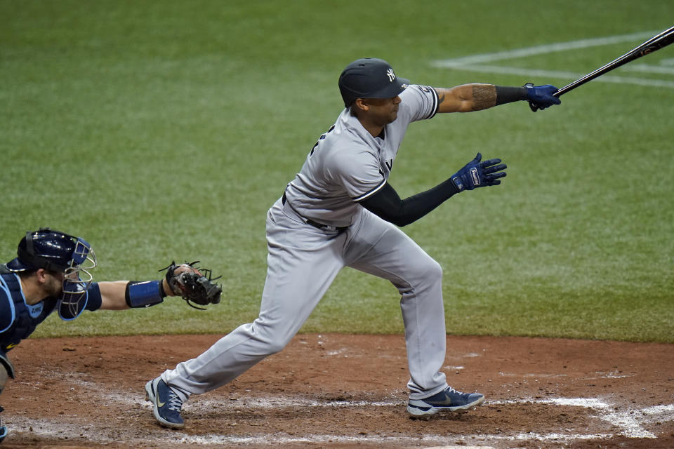New York Yankees' Aaron Hicks follows he flight of his run-scoring sacrifice fly off Tampa Bay Rays relief pitcher Jeffrey Springs during the seventh inning of a baseball game Wednesday, May 12, 2021, in St. Petersburg, Fla. Yankees' Aaron Judge scored. (AP Photo/Chris O'Meara)
