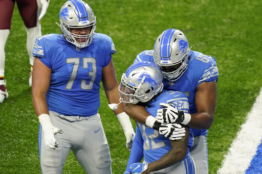 Detroit Lions running back D'Andre Swift (32) is congratulated on his touchdown by teammates offensive guard Jonah Jackson (73) and offensive tackle Tyrell Crosby (65) during the second half of an NFL football game against the Washington Football Team, Sunday, Nov. 15, 2020, in Detroit. (AP Photo/Carlos Osorio)