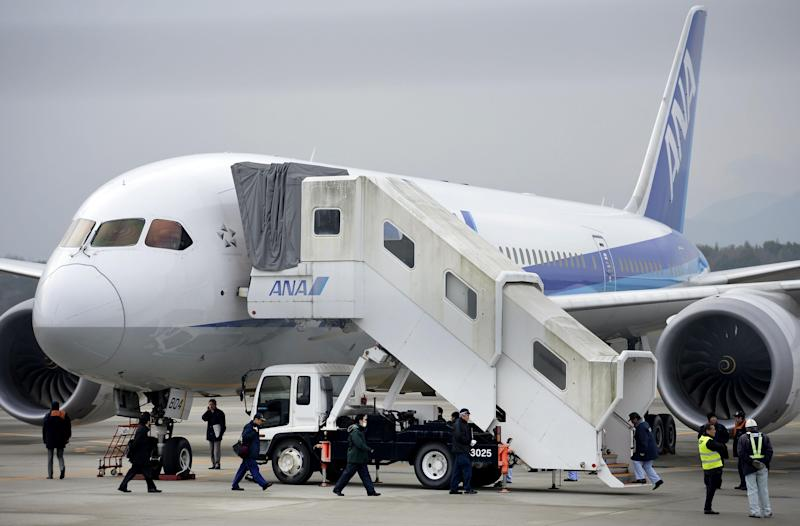 FILE - In this Jan. 17, 2013 file photo, officials examine an All Nippon Airways 787 a day after it made an emergency landing at Takamatsu airport in Takamatsu, western Japan. A probe into the overheating of a lithium ion battery in the All Nippon Airways Boeing 787 found it was improperly wired, Japan's Transport Ministry said Wednesday, Feb. 20, 2013. (AP Photo/Kyodo News) JAPAN OUT, MANDATORY CREDIT, NO LICENSING IN CHINA, HONG KONG, JAPAN, SOUTH KOREA AND FRANCE