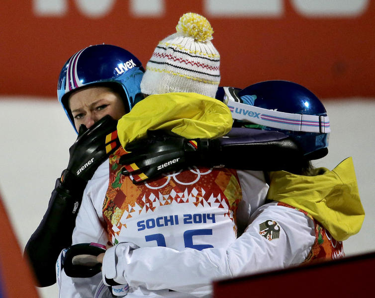 Germany's Carina Vogt, left, is hugged by teammates after winning the gold during the women's normal hill ski jumping final at the 2014 Winter Olympics, Tuesday, Feb. 11, 2014, in Krasnaya Polyana, Russia. (AP Photo/Charlie Riedel)