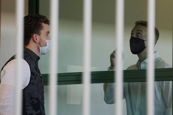 Finnegan Lee Elder, right, points the sky after showing a crucifix to co-defendant Gabriel Natale-Hjorth before a jury began deliberating their fate (AP)
