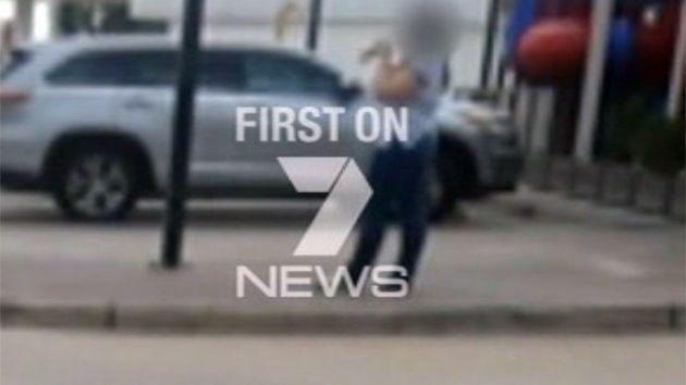 Courtney Topic standing outside the Hungry Jack's, a playground in the background, with the large knife in her hand. Photo: 7News