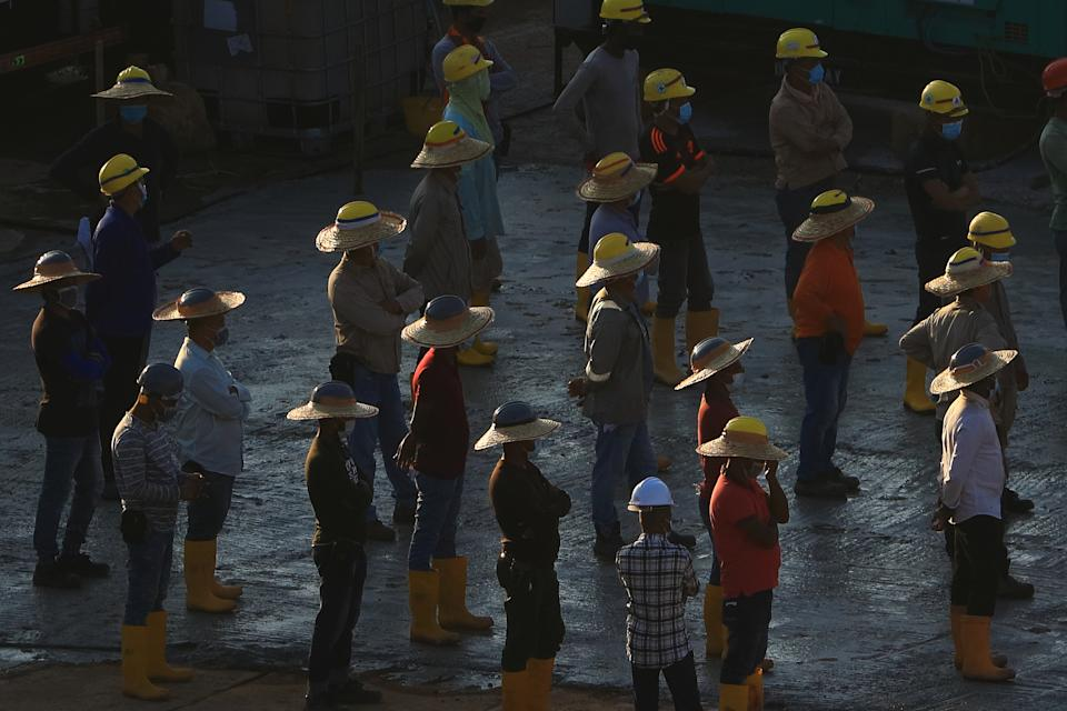 Workers wearing protective mask assemble for a briefing at a construction site of a quick-build dormitory on 9 June, 2020 in Singapore. (PHOTO: Getty Images)