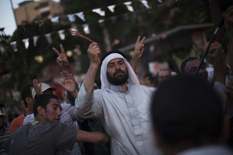 """Supporters of the ousted Egypt's President Mohammed Morsi dance during a protest in Nasr City, a suburb of Cairo, Egypt, Tuesday July 9, 2013. After days of deadlock, Egypt's military-backed interim president named a veteran economist as prime minister on Tuesday and appointed pro-democracy leader Mohamed ElBaradei as a vice president, while the army showed its strong hand in shepherding the process, warning political factions against """"maneuvering"""" that impedes the transition. (AP Photo/Manu Brabo)"""