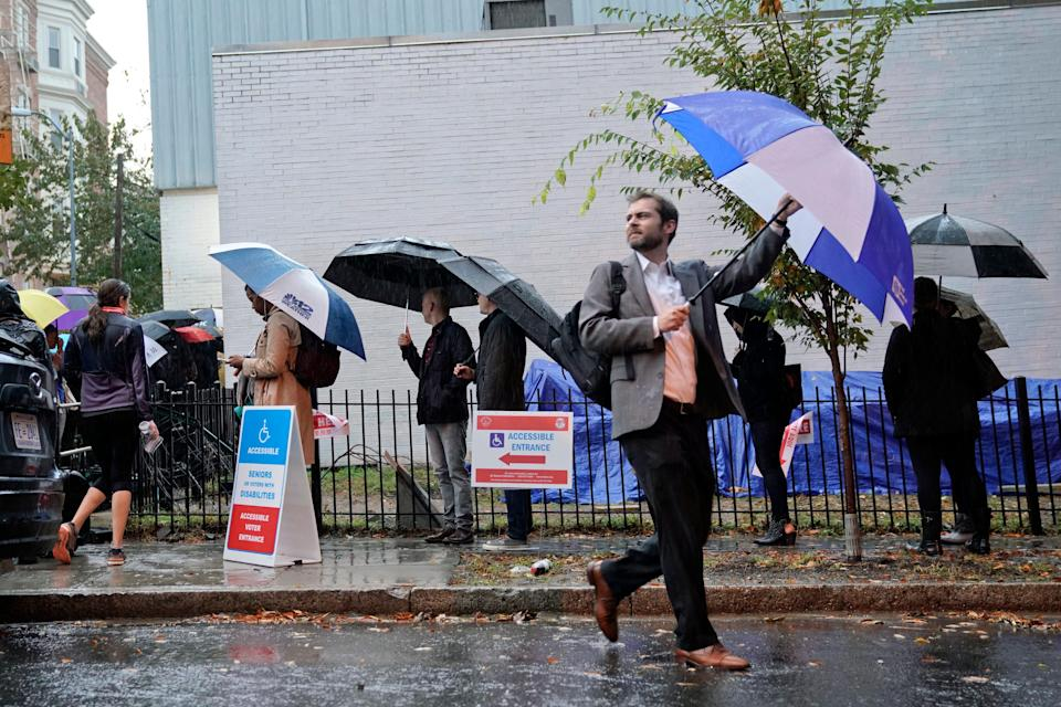Voters line up in the rain outside Bright Family and Youth Center in the Columbia Heights neighborhood in Washington, Tuesday, Nov. 6, 2018.