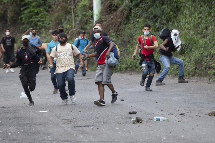 Honduran migrants throw stones toward Guatemalan soldiers and police blocking them from advancing toward the US, on the highway in Vado Hondo, Guatemala, Monday, Jan. 18, 2021. The roadblock was strategically placed at a chokepoint on the two-lane highway flanked by a tall mountainside and a wall leaving the migrants with few options. (AP Photo/Sandra Sebastian)