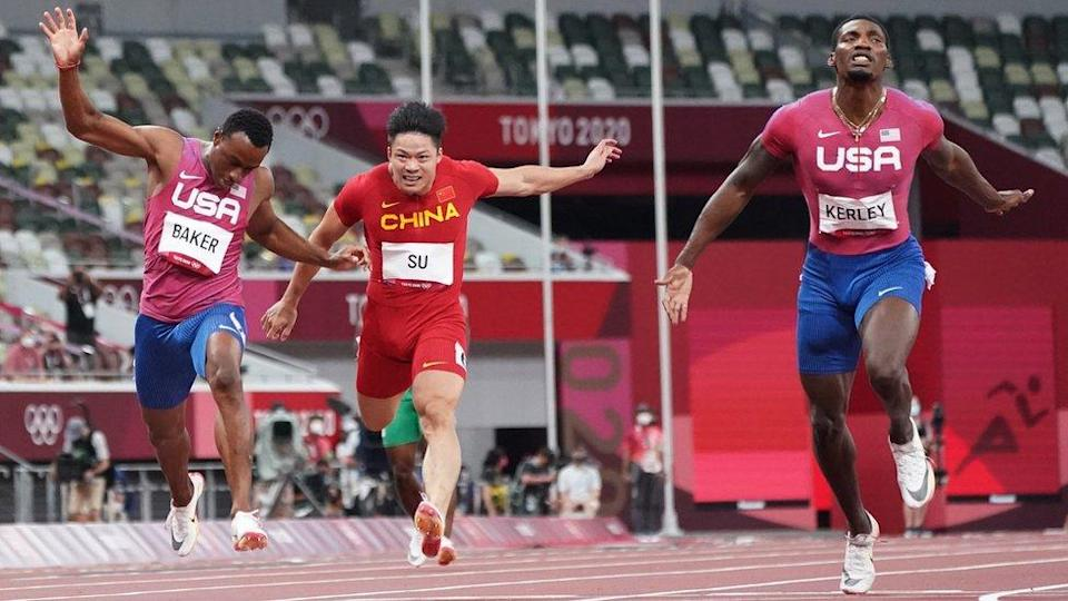 """Tokyo 2020 Olympics - Athletics - Men""""s 100m - Final - OLS - Olympic Stadium, Tokyo, Japan - August 1, 2021. Su Bingtian of China and Ronnie Baker of United States and Fred Kerley of the United States crossing the line"""