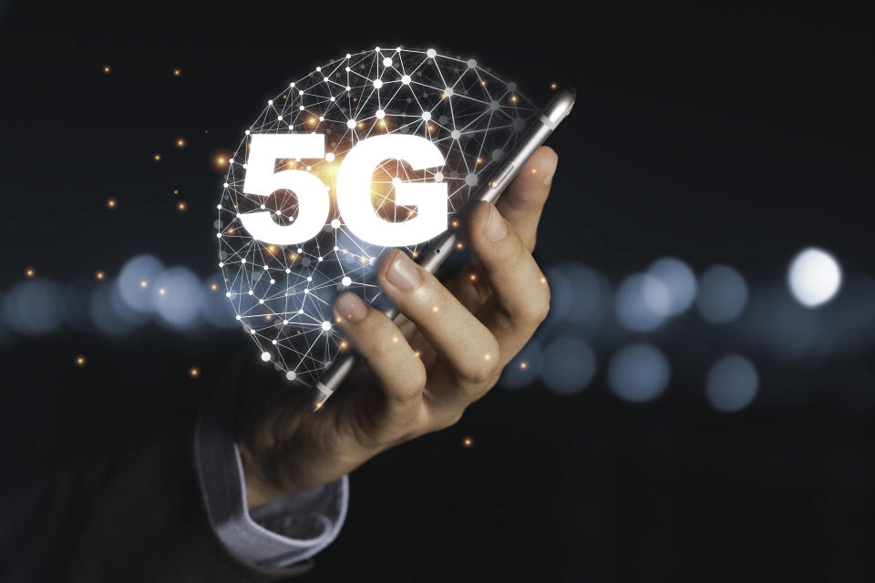 Businessman holding mobile phone with 5G infographic. 5 Generation wireless technology of mobile signal which big change for internet of thing.