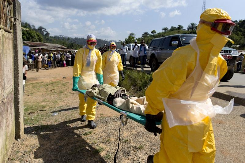 Health workers in protective suits carry a patient suspected of having Ebola, on their way to a treatment centre in Macenta, Guinea, on November 21, 2014 (AFP Photo/Kenzo Tribouillard)