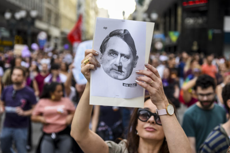 """29 September 2018, Brazil, Curitiba: A demonstrator holds up a poster in which the far-right presidential candidate Bolsonaro (l) equates Hitler with Hitler. Numerous people took to the streets against Bolsonaro and his racist, anti-woman and anti-gay course. The ex-military is the favourite in the presidential election on 7 October. Bolsonaro is known for ranting against homosexuals and blacks and glorifying the military dictatorship (1964-1985). Again and again he shocks with verbal derailments. He once certified to a politician that she did not deserve to be raped """"because she is very ugly"""". Photo: Henry Milleo/dpa (Photo by Henry Milleo/picture alliance via Getty Images)"""