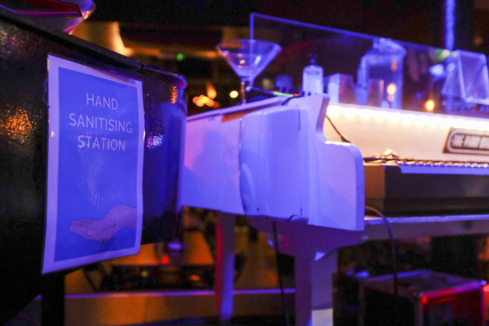 """A sign reading 'hand sanitizing station' at The Piano Works club in Farringdon, London, Friday, July 16, 2021, ahead of its reopening as part of the relaxation of COVID-19 restrictions. Thousands of young people plan to dance the night away at """"Freedom Day"""" parties as the clock strikes midnight Monday, when almost all coronavirus restrictions in England are due to be scrapped. Nightclubs can open fully and are not required to use vaccine passports. (AP Photo/Alberto Pezzali)"""