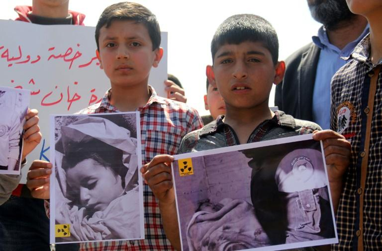 Residents of Khan Sheikhun hold placards and pictures on April 7, 2017, during a protest condemning a suspected chemical weapons attack on their town that killed at least 86 people, among them 30 children