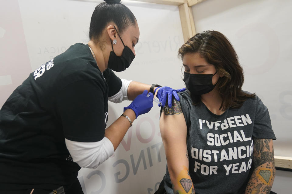 Denise Padilla, right, an instructor at the culinary school at Eva's Village, is vaccinated in Secacus, N.J., Sunday, Feb. 28, 2021. In an effort to vaccinate undeserved populations, Riverside Medical Group partnered with Eva's Village, an anti-poverty non-profit, to help vaccinate over 80 of their clients and staff members. (AP Photo/Seth Wenig)