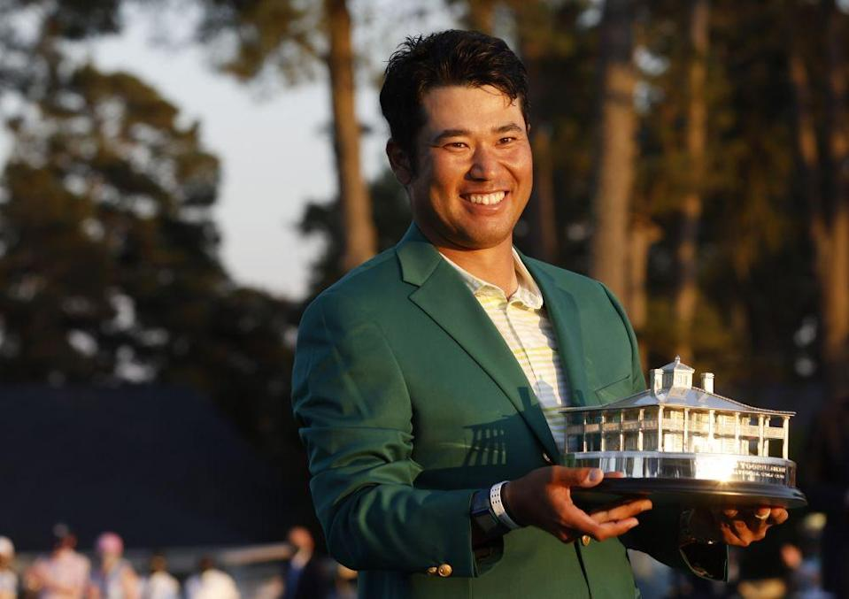 Japan's Hideki Matsuyama celebrates with the green jacket and the trophy after winning The Masters at the Augusta National Golf Club April 11, 2021. — Reuters pic
