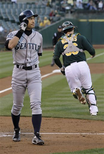 Seattle Mariners right fielder Ichiro Suzuki, left, walks to the dugout after striking out against Oakland Athletics pitcher Tommy Milone during the second inning of a baseball game in Oakland, Calif., Friday, July 6, 2012. At right is Athletics catcher Derek Norris. (AP Photo/Jeff Chiu)