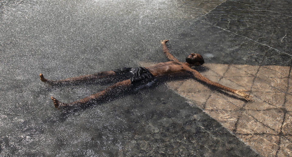 A man cools down in a water feature.