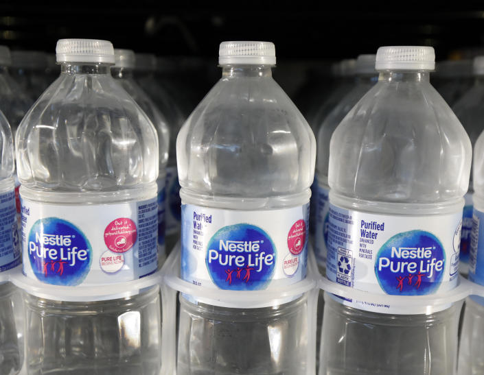 FILE - In this Sept. 21, 2018, file photo, is a closeup of pint bottles of purified water, Pure Life, manufactured by Nestle, on sale in a Ridgeland, Miss., convenience store. Global food giant Nestle is selling its North American bottled-water brands for $4.3 billion to a pair of private-equity firms that hope to reinvigorate sales. Brands including Poland Spring, Deer Park, Arrowhead and Pure Life will be sold to a subsidiary of One Rock Capital Partners in partnership with Metropoulos & Co. (AP Photo/Rogelio V. Solis, File)