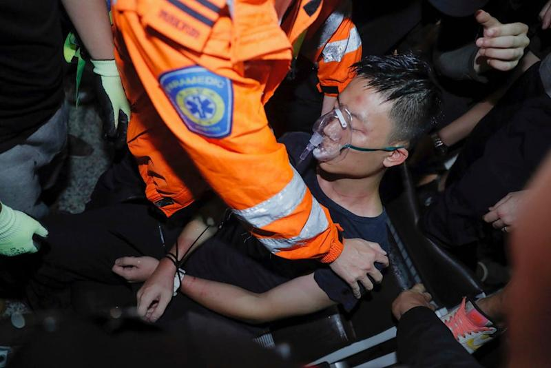 A medical staffer helps a detained man at Hong Kong International Airport who protesters claimed was a police officer from mainland China on Tuesday, Aug. 13, 2019. (AP Photo/Kin Cheung)