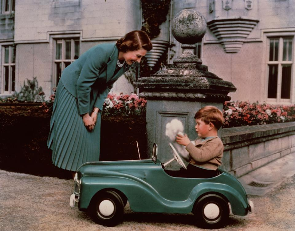 Then-Princess Elizabeth watching Prince Charles play in a toy car while at Balmoral inSeptember 1952.