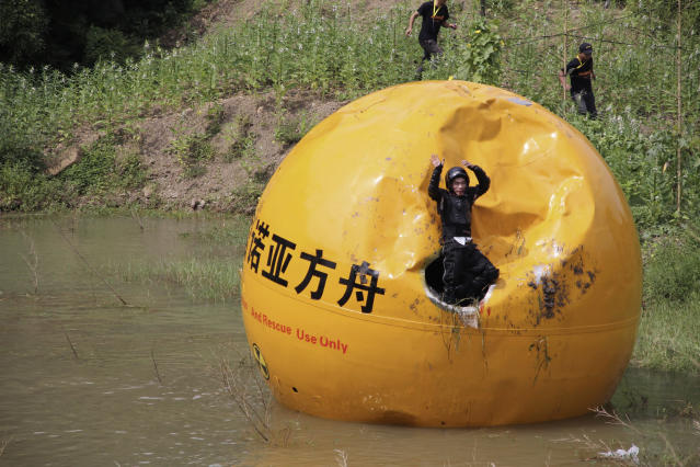 A Chinese inventor, Yang Zongfu celebrates on his six-ton (5,443 kg) ball container named Noah's Ark of China after he succeeds in a series of tests of the vessel in Yiwu, Zhejiang province, August 6, 2012. According to local media, Yang spent two years and 1.5 million RMB (235,585 USD) to build this four-metre diameter vessel, which has been tested capable of housing a three-person family and sufficient food for them to live in 10 months. The vessel was designed to protect people inside from external heat, water and external impact. Picture taken August 6, 2012. REUTERS/China Daily