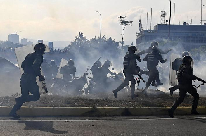 Members of the Bolivarian National Guard loyal to Venezuelan President Nicolas Maduro run under a cloud of tear gas after being repelled with rifle fire by guards supporting Venezuelan opposition leader and self-proclaimed acting president Juan Guaido in front of La Carlota military base in Caracas on April 30, 2019.(Photo: Yuri Cortez/AFP/Getty Images)
