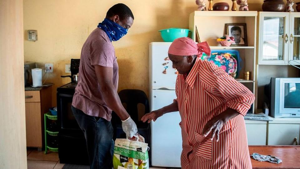 A volunteer from the Rays of Light NGO (L) delivers food and cleaning products to an elderly woman (R) living alone in Alexandra, Johannesburg, on April 16, 2020.