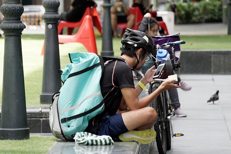 A food delivery rider checks his phone while having a meal at the Raffles Place Park on 7 April 2020, the first day of Singapore's month-long circuit breaker period. (PHOTO: Dhany Osman / Yahoo News Singapore)