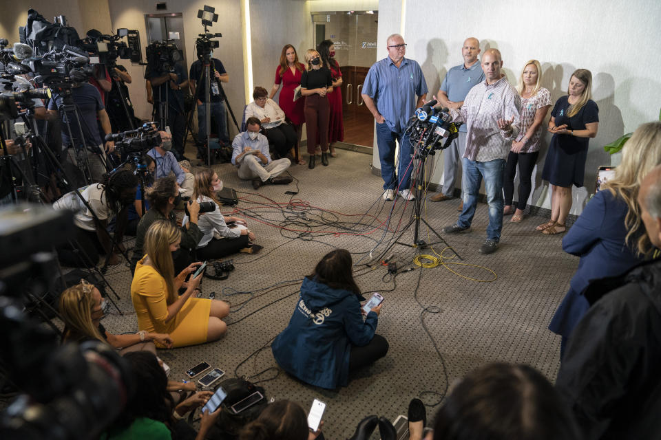 Jim Schmidt, stepfather of Gabby Petito, whose death on a cross-country trip has sparked a manhunt for her boyfriend Brian Laundrie, speaks alongside Joseph Petito, father, immediate left, Tara Petito, stepmother, second from right, and Nichole Schmidt, mother, right, during a news conference, Tuesday, Sept. 28, 2021, in Bohemia, N.Y. (AP Photo/John Minchillo)