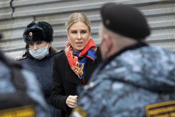 Russian opposition activist Lyubov Sobol, center, walks to the court escorted by police and Russian Federal Bailiffs service officers in Moscow, Russia, Monday April 5, 2021. A Moscow court will start considering the case against Navalny ally Lyubov Sobol, who is charged with unlawful entry into a dwelling. In December Sobol rang the doorbell of a flat of a relative of an alleged FSB agent Konstantin Kudryavtsev, whom Navalny accused of his poisoning. (AP Photo/Pavel Golovkin)