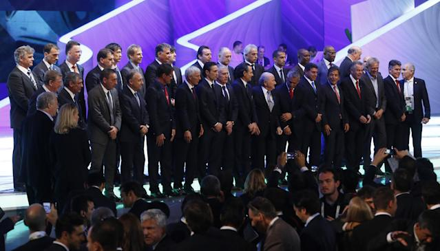 The coaches of the national team pose for a group photo with FIFA President Joseph Blatter, center, after the draw ceremony for the 2014 soccer World Cup in Costa do Sauipe near Salvador, Brazil, Friday, Dec. 6, 2013. (AP Photo/Victor R. Caivano)