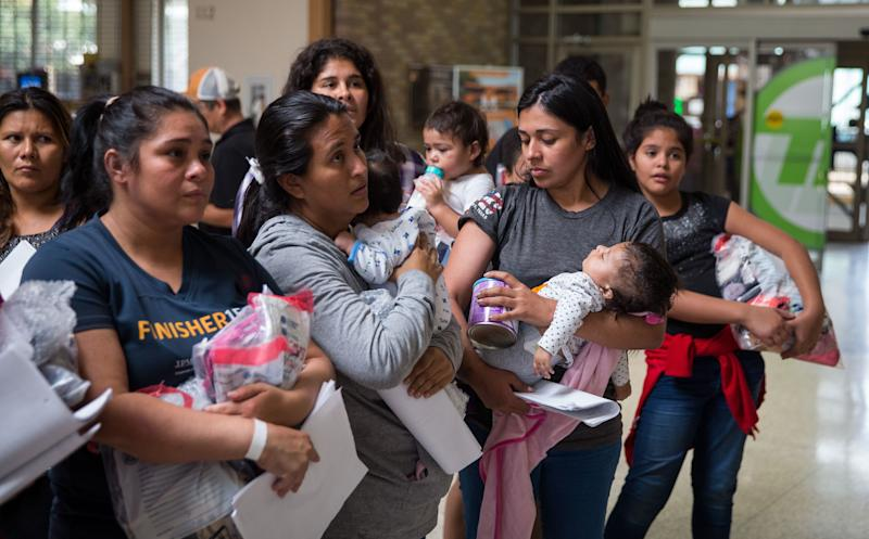 """Immigrants wait to head to a nearby Catholic Charities relief center after being dropped off at a bus station shortly after release from detention through """"catch and release"""" immigration policy on June 17 in McAllen, Texas. (Photo: Loren Elliott/Getty Images)"""