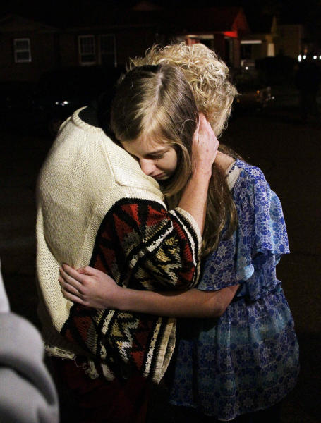 Unidentified friends of the pilot of a small plane that authorities say crashed into a west Jackson, Miss., home shortly after 5 p.m. Tuesday evening, Nov. 13, 2012, hug each other as they await information as to the pilot and passengers. The home's resident is believed to have escaped but authorities have not released names of plane's passengers. (AP Photo/Rogelio V. Solis)