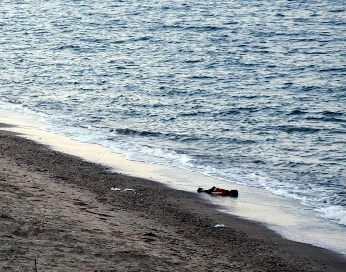 In this Sept. 2, 2015 file photo, lifeless body of three-year-old Syrian migrant boy, Aylan Kurdi, lies on the sea shore, near the beach of Aegean resort of Bodrum, Turkey. Aylan with members of his family fled the war in Syria, and died on the final stretch of the arduous journey to safety in Europe when the overcrowded rubber dinghy he was in capsized after leaving Turkey. His mother and five-year-old brother also died that day.(Zergun Dincer, Depo Photos via AP, File )