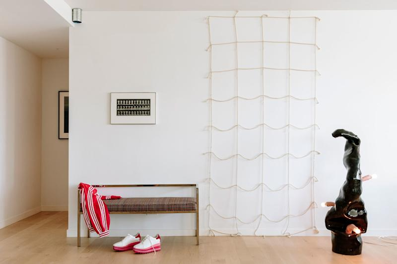Japanese artist Jiro Takamatsu's netlike work on the wall from 1970 was acquired by Jessica's grandparents when it was made. The couple upholstered a Swaim bench in a punchy Knoll fabric.