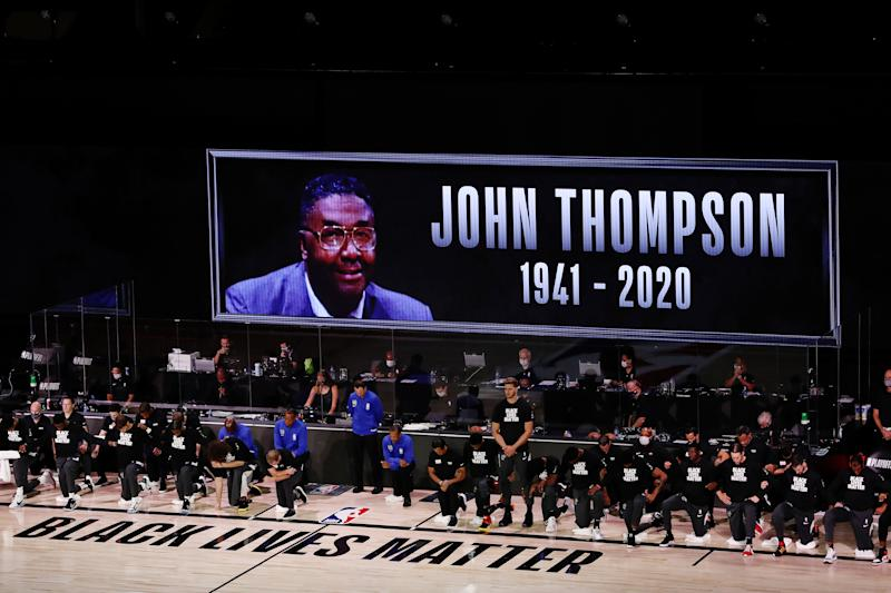 LAKE BUENA VISTA, FLORIDA - AUGUST 31: The Miami Heat and Milwaukee Bucks take a knee during the National Anthem and as a John Thompson tribute screen is displayed prior to Game One of the Eastern Conference Second Round during the 2020 NBA Playoffs at the Field House at ESPN Wide World Of Sports Complex on August 31, 2020 in Lake Buena Vista, Florida. NOTE TO USER: User expressly acknowledges and agrees that, by downloading and or using this photograph, User is consenting to the terms and conditions of the Getty Images License Agreement. (Photo by Mike Ehrmann/Getty Images)