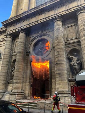 A member of the fire brigade reacts as Saint-Sulpice church is seen on fire in Paris, France, March 17, 2019 in this still image taken from social media obtained on March 18, 2019.  INSTAGRAM @agneswebste/via REUTERS via REUTERS ATTENTION EDITORS - THIS IMAGE HAS BEEN SUPPLIED BY A THIRD PARTY. MANDATORY CREDIT. NO RESALES. NO ARCHIVES