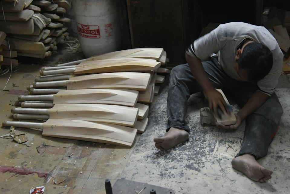 <p>An Indian craftsman works on unfinished cricket bats in a factory in Meerut</p> (AFP via Getty Images)
