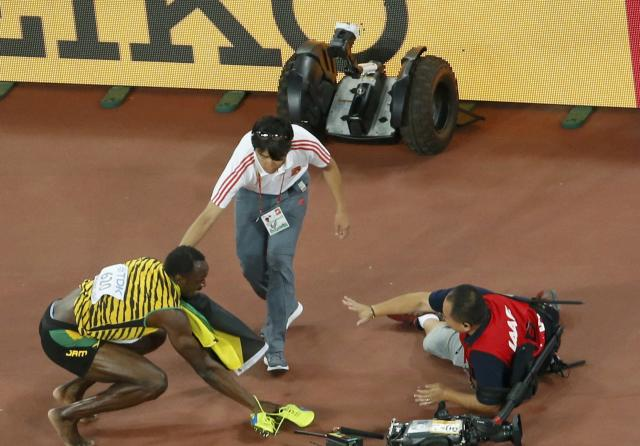 Winner Bolt of Jamaica crouches after being hit by a cameraman on a Segway after competing at the men's 200 metres final during the 15th IAAF World Championships at the National Stadium in Beijing