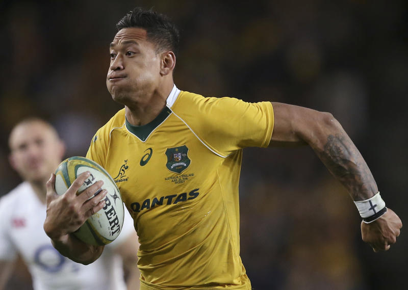 """In this June 25, 2016, photo, Australian rugby union player Israel Folau, wearing tape on his wrist adorned with a cross, runs toward the try line to score against England during their rugby union test match in Sydney. Folau, one of the sport's top players, published a message on his Instagram account that said """"drunks, homosexuals, adulterers, liars, fornicators, thieves, atheists, idolators. Hell awaits you."""" (AP Photo/Rick Rycroft)"""