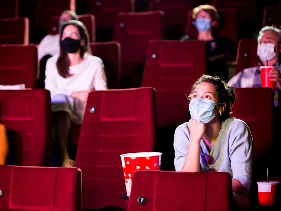 Audience at the cinema wearing protective masks and sitting in a socially-distanced manner (iStock/Getty Images)