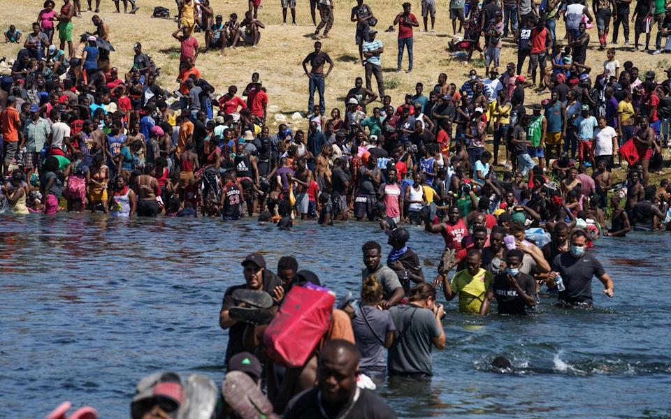 Haitian migrants, part of a group of over 10,000 people staying in an encampment on the US side of the border, cross the Rio Grande river to get food and water in Mexico - PAUL RATJE/AFP via Getty Images