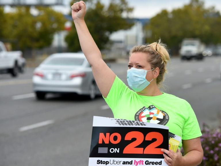 """Rideshare driver Erica Mighetto shouts to motorists while urging a """"No"""" vote on Proposition 22 in Oakland, California on October 09, 2020"""